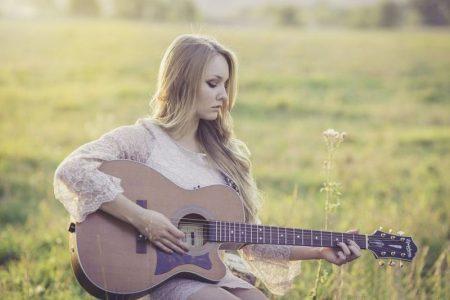 femme jouant de la guitare dans un champs