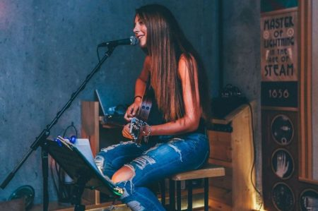 femmedonnant un concert de guitare