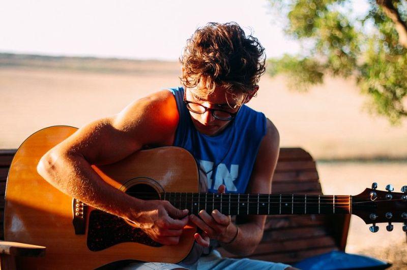garcon jouant de la guitare en exterieur